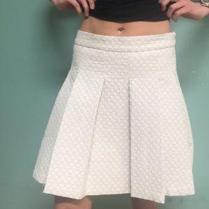A line pleated ivory mid length skirt.